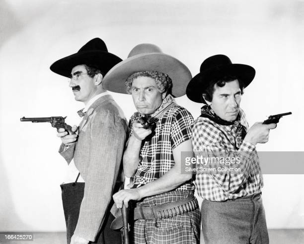 The Marx Brothers Groucho Marx Harpo Marx and Chico Marx pose holding toy pistols and wearing cowboy outfits circa 1935