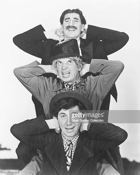 The Marx Brothers Groucho Marx Harpo Marx and Chico Marx US comedians covering their ears in a studio portrait against a white background circa 1935