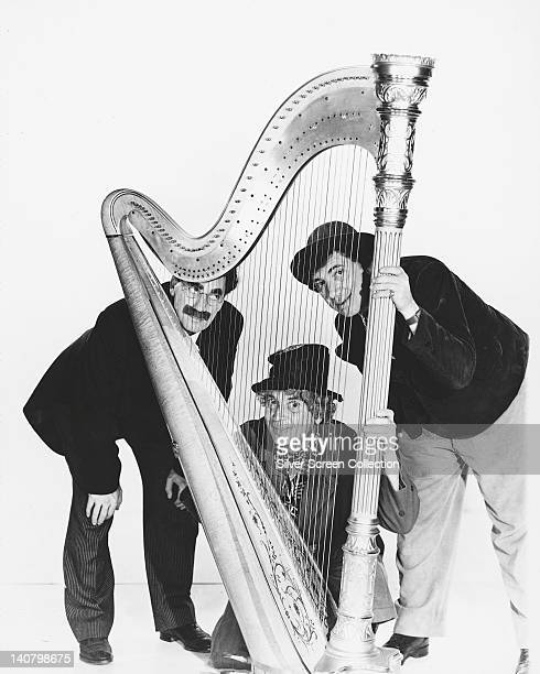 The Marx Brothers Groucho Marx Harpo Marx and Chico Marx US comedians posing with a harp in a studio portrait against a white background circa 1935