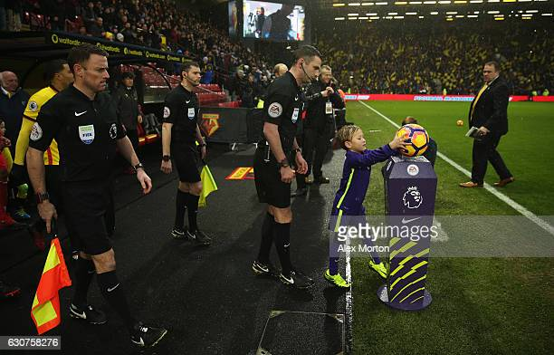 The mascot collects the match ball alongside referee Michael Oliver prior to during the Premier League match between Watford and Tottenham Hotspur at...