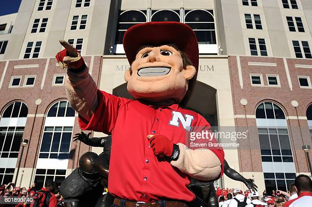 The mascot of Nebraska Cornhuskers greets the team in front of the stadium before the game against the Wyoming Cowboys at Memorial Stadium on...