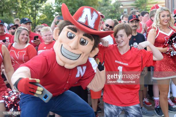The mascot of the Nebraska Cornhuskers takes a photo with a young fan before the game against the Akron Zips at Memorial Stadium on September 1 2018...