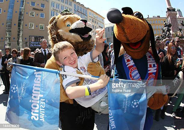 The mascots Olympi and Bavarian Lion have fun with a little fan during the UEFA Champions League Trophy Tour Final at Marienplatz on May 14, 2012 in...