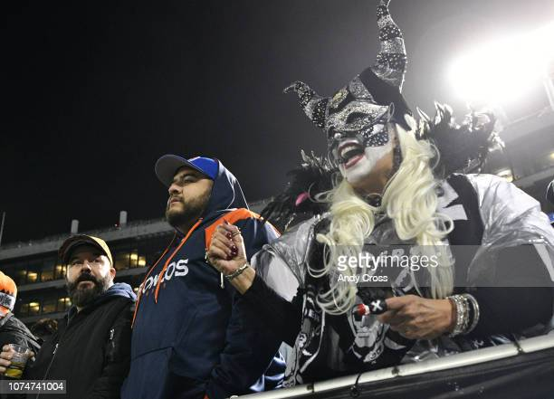 The MaskaRaider Oakland Raiders super fan cheers for her team alongside of Denver Broncos fan Leo Garcia center during the first half of the game at...