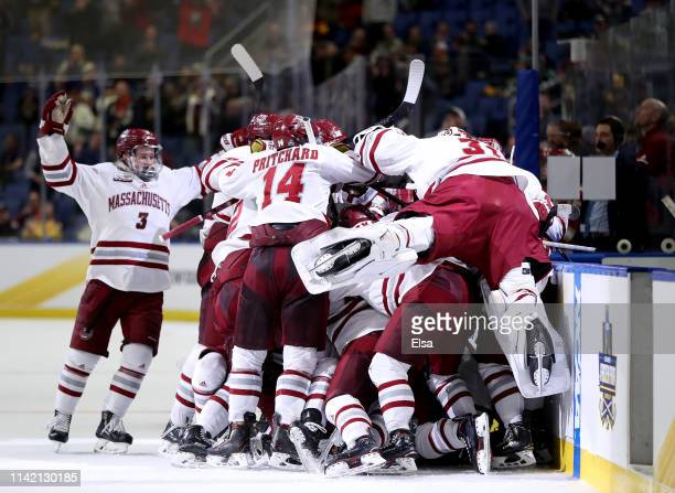 The Massachusetts Minutemen celebrate the overtime win over Denver Pioneers during the semifinals of the NCAA Men's Frozen Four at KeyBank Center on...