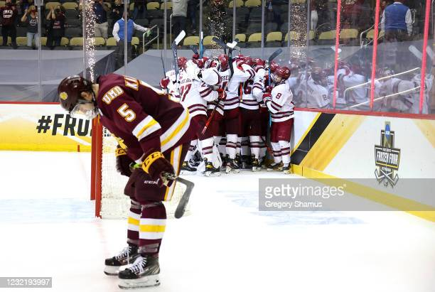 The Massachusetts Minutemen celebrate their 5-4 overtime win against the Minnesota Duluth Bulldogs during the Division I Men's Ice Hockey Semifinals...