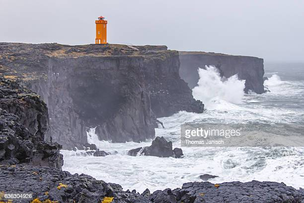The massive cliffs, rough waters and old lighthouse at Svörtuloft, Snaefellsnes Peninsula