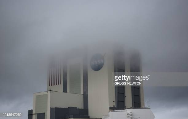 The massive Vehicle Assembly Building is shrouded in fog as stormy weather greeted launch day at the Kennedy Space Center in Florida on May 27 2020 A...