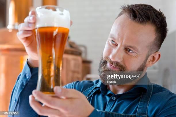 il maestro birraio che tiene il bicchiere di birra nel suo micro birrificio - izusek foto e immagini stock