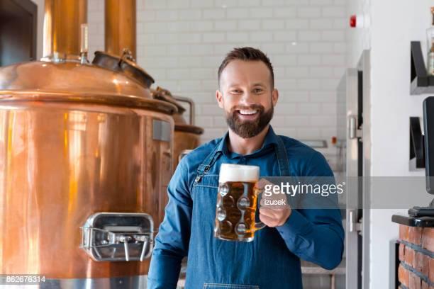 o mestre cervejeiro segurando a caneca de cerveja em seu micro cervejaria - izusek - fotografias e filmes do acervo