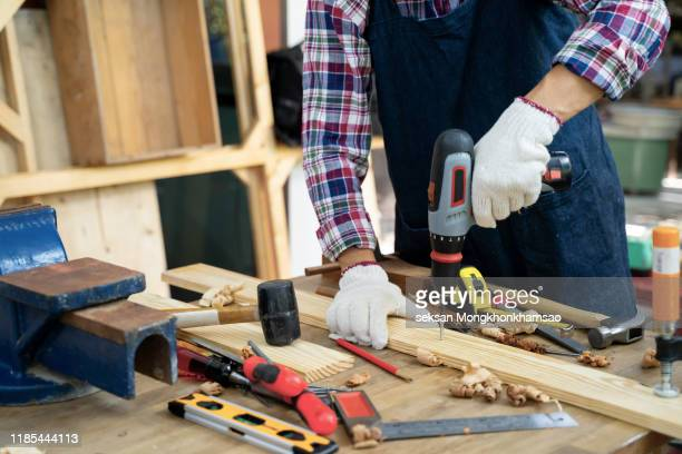 the master works in a studio and drill a hole in a wooden board. - diy stock pictures, royalty-free photos & images