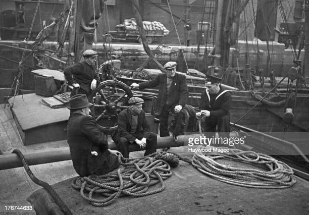 The masters and mates of two Thames sailing barges talking to a naval rating London 1943 Original publication Picture Post Barge Series unpub