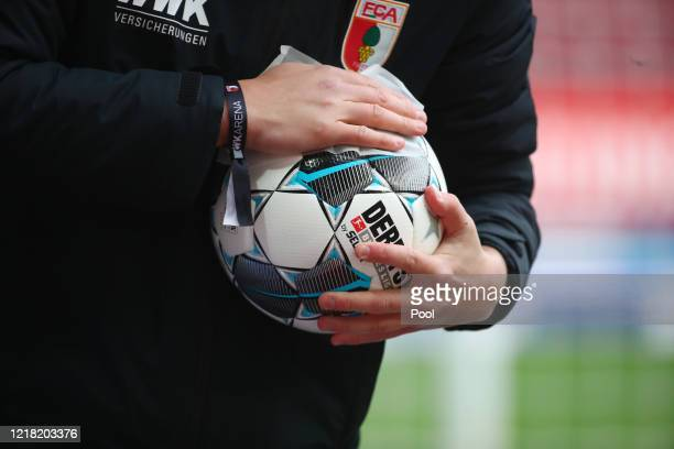 The match ball is cleaned at half time during the Bundesliga match between FC Augsburg and 1. FC Koeln at WWK-Arena on June 7, 2020 in Augsburg,...