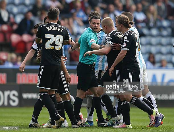 The match referee intervenes during a dispute between Nico Yennaris of Brentford FC and Dean Whitehead of Huddersfield Town FC during the Sky Bet...