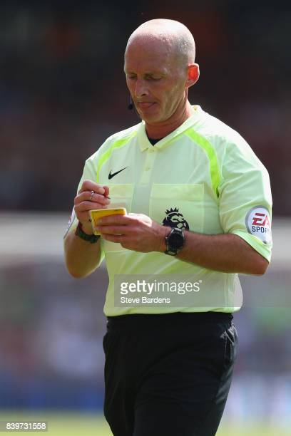 The match referee Mike Dean takes a name during the Premier League match between AFC Bournemouth and Manchester City at Vitality Stadium on August 26...