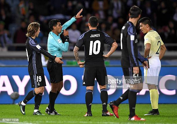 The match referee refers a decision to the video assistant referee during the FIFA Club World Cup Semi Final match between Club America and Real...