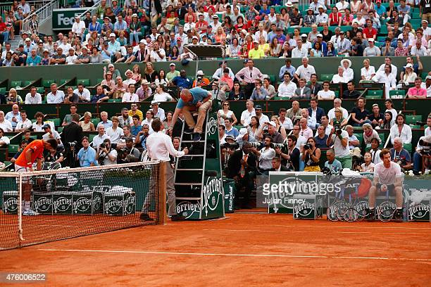 The match referee speaks to the chair umpire as bad weather stops play in the fourth set of the Men's Semi Final match between Andy Murray of Great...