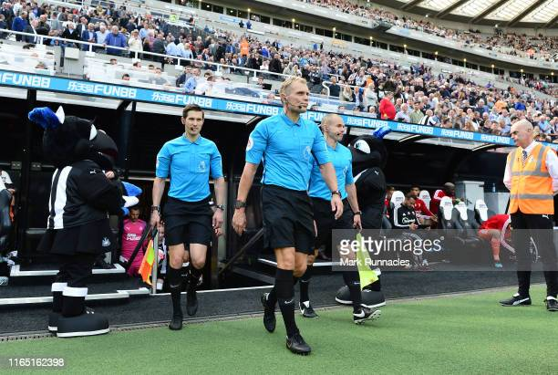 The match refereeing team of referee Graham Scott assistant referee Neil Davies and assistant referee Adrian Holmes lead out the teams ahead of the...