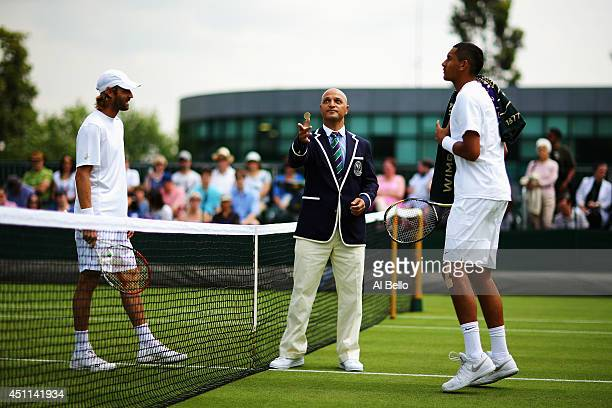 The match umpire preforms the coin toss as Nick Kyrgios of Australia and Stephane Robert of France look on prior to their Gentlemen's Singles first...