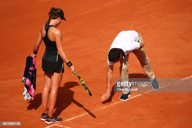 The match umpire shows Johanna Konta of Great Britain a ball mark on the court during her ladies singles first sound match against Yulia Putintseva...