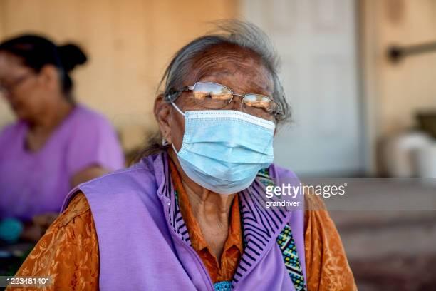 予約の彼女の家でマスクを身に着けているナバホ一家の母長、モニュメントバレー、covid19 - ナバホ文化 ストックフォトと画像