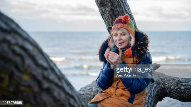 the mature 55 years old woman drinking a hot tea, resting on the baltic sea shore with her zennenhund dog. - 55 59 years stock pictures, royalty-free photos & images