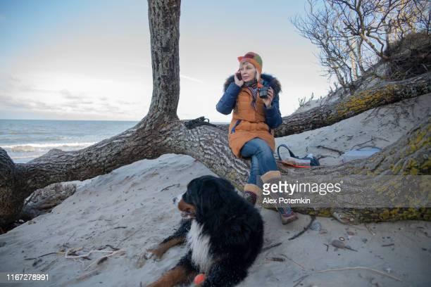la mujer madura de 55 años hablando a través de un teléfono inteligente y bebiendo un té caliente, descansando en la orilla del mar báltico con su perro zennenhund. - 50-59 years and women only fotografías e imágenes de stock