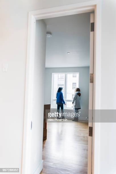 the mature attractive woman, the single mother, and her daughters looking around the new empty apartment. - alex potemkin or krakozawr stock pictures, royalty-free photos & images