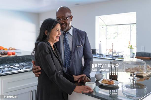the mature couple talking, have breakfast and getting ready to go outside - 50 59 years stock pictures, royalty-free photos & images