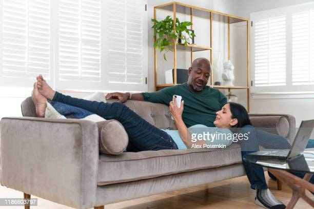 the mature happy family couple resting in the living room. the man sitting on a couch, the woman lying down with her head on his laps and using a smartphone. - 50 59 years stock pictures, royalty-free photos & images