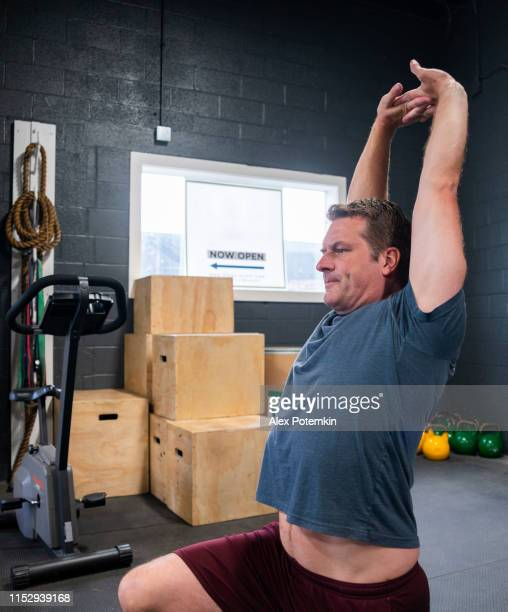 the mature latino man doing stretching exercise in the gym - alex potemkin or krakozawr latino fitness stock photos and pictures