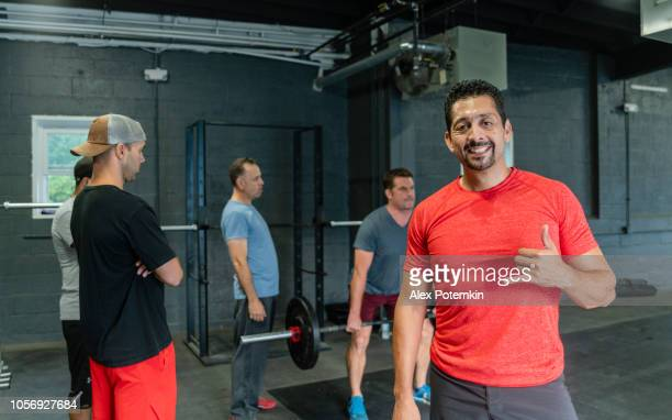 the mature latino man posing in front of the group of his friends, athletes of different ages, body types and abilities, in the gym - alex potemkin or krakozawr latino fitness stock photos and pictures