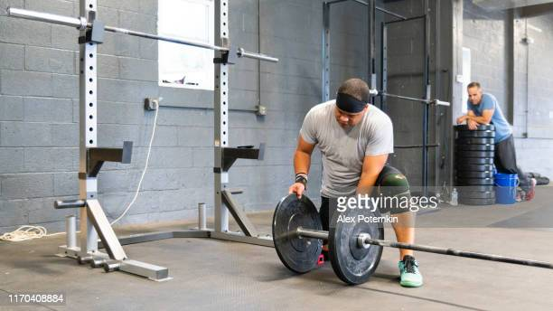 the mature latino man preparing the equipment to the weight exercise in the gym. - alex potemkin or krakozawr latino fitness stock photos and pictures