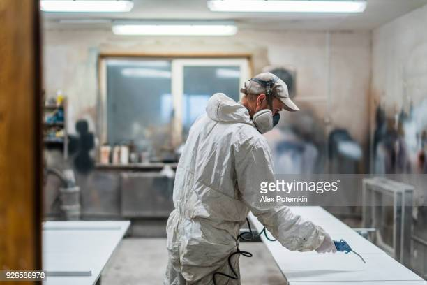 the mature man, manual worker, wearing the protective mask and coveralls, cleaning surfaces for painting with the compressed air gun - air respirator mask stock pictures, royalty-free photos & images