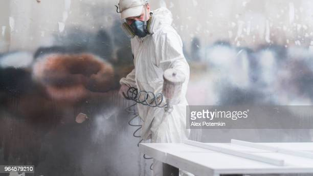 the mature man wearing protective mask and coveralls painting the furniture's details at the small manufacture - alex potemkin or krakozawr stock pictures, royalty-free photos & images