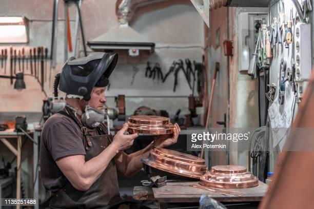 den mogna mannen, svetsare med svets masken öppen arbetar på mässings detaljer-kontroll och förberedelse för elektrisk svetsning - don smith bildbanksfoton och bilder