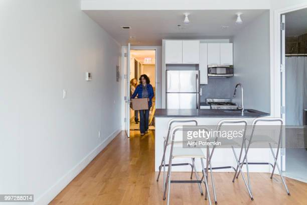 the mature woman moving cardboard boxes with stuff into the new apartment in brooklyn - alex potemkin or krakozawr stock pictures, royalty-free photos & images