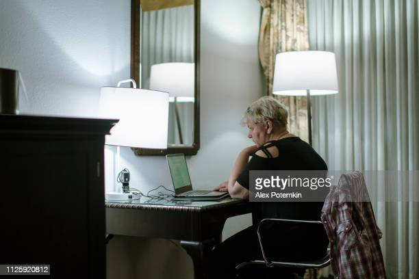 The mature woman working online with the laptop from the motel room