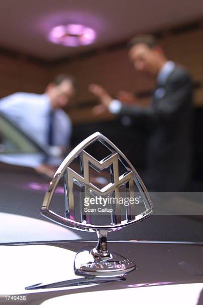 The Maybach hood ornament is visible as a salesman shows a potential customer details of a Maybach 57 limousine which retails for EUR 359...