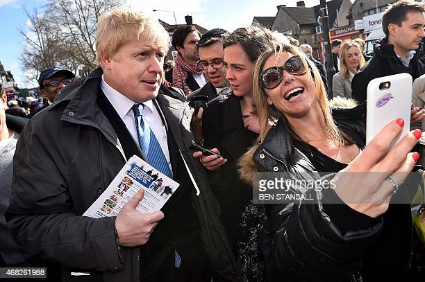 The Mayor of London Boris Johnson poses for a selfie with a member of the public on a visit to the Hendon constituency in north west London on April...