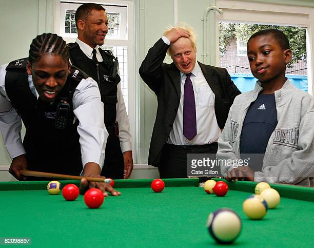 The Mayor of London Boris Johnson shares a joke with a police officer while visiting young people at Brixton Youth Centre on July 29 2008 in London...