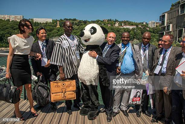 The mayor of Lyon Gerard Collomb with a WWF panda mascot presents the new area of Lyon to foreign mayors gathered to address climate change on July 1...