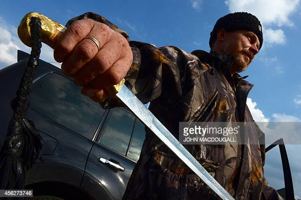 The mayor of Pervomaisk a Cossack commander named 'Evgeniy' poses with his traditional sword in Pervomaisk some 50 km west of Lugansk September 28...