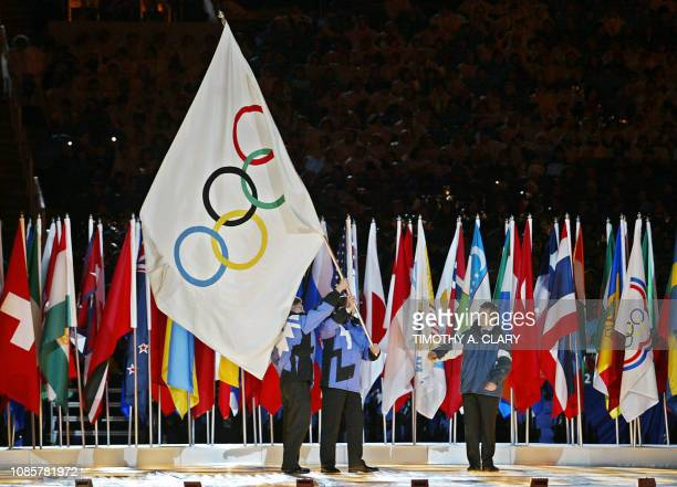 The Mayor of Salt Lake City Rocky Anderson passes the Olympic flag to the president of the International Olympic Committee Jacques Rogge who will...