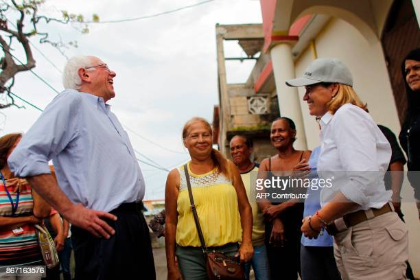 The mayor of San Juan Carmen Yulin laughs with US Sen Bernie Sanders during a visit to the Playita community in San Juan Puerto Rico October 27 2017...