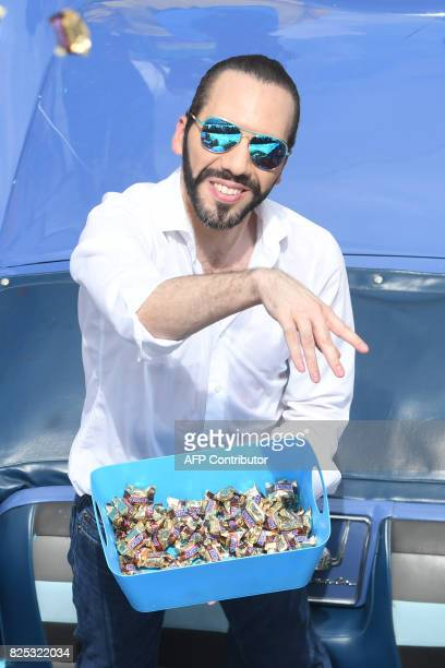 The Mayor of San Salvador Nayib Bukele throws candy during a parade marking the start of San Salvador's patron saint's festival in honor of Divino...