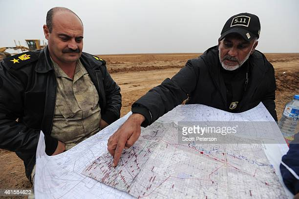 The mayor of the Iraqi city of Khalis, Uday al-Khadran , looks at a map with Iraqi Army Colonel Saad Mirwah while overseeing the building of a new...