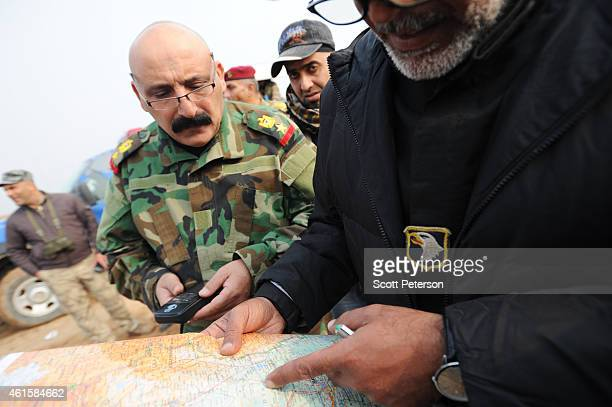 The mayor of the Iraqi city of Khalis, Uday al-Khadran , looks at a map with Iraqi Army officers while overseeing the building of a new dirt road...