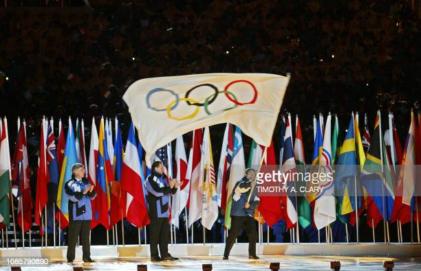 The Mayor of Torino Sergio Chiamparino waves with the Olympic flag as the Mayor of Salt Lake City Rocky Anderson and the president of the...