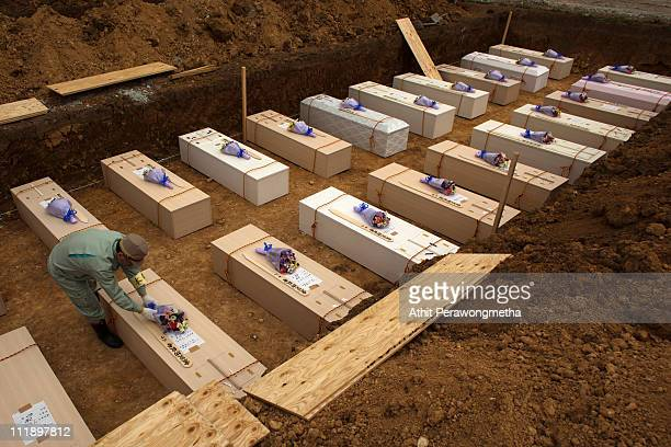 The mayor of Yamamoto places flowers on the coffin of an unidentified earthquake victim during a mass funeral on April 8, 2011 in Yamamoto, Miyagi...